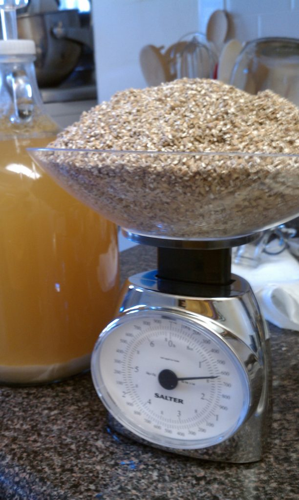 Grain on a scale with a fermented beer in the background